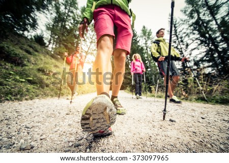 Group of hikers with backpacks and sticks walking on a mountain at sunset - Four friends making an excursion in the nature - stock photo