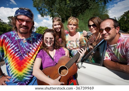 Group of hippies with female guitar player - stock photo