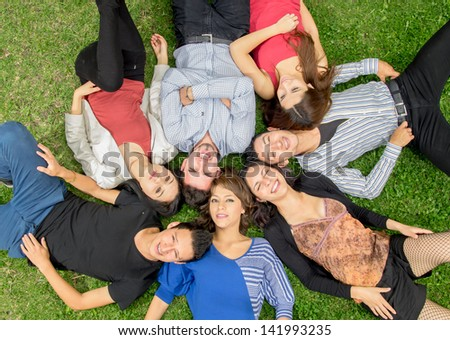 Group of hispanic friends laying down in park - stock photo