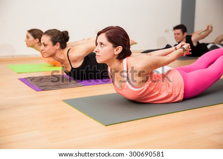 Group of Hispanic people doing the locust pose with interlaced hands in a yoga studio - stock photo