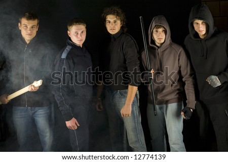 Group of hooligans. They are looking at camera and standing in dark place. Front view - stock photo