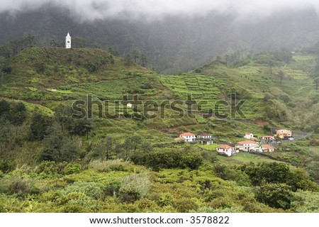 Group of houses and a church in Madeira's mountains - stock photo