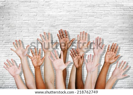 Group of human arms raised with brick wall. - stock photo