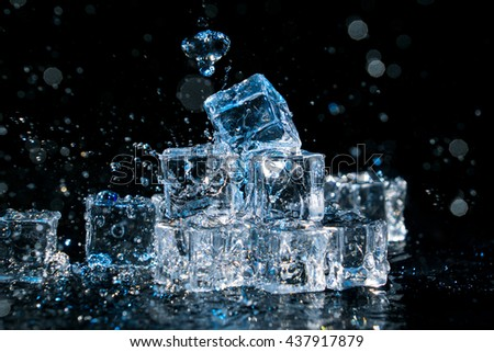 Group of ice cubes with many water splashes on black background. - stock photo