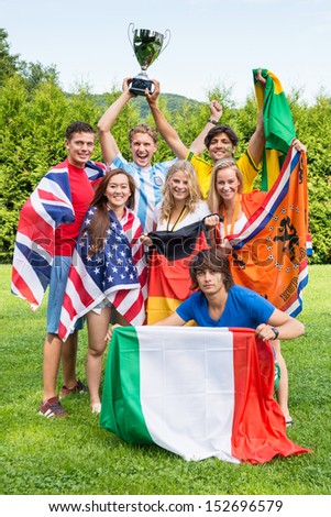 Group of international sports fans, each dressed in the color of their country and carrying the their nation's flag winning the cup together. Sportivity, friendship and globalization theme - stock photo