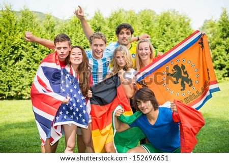 Group of international sports fans, each dressed in the color of their country and carrying the their nation's flag. Sportivity, friendship and globalization theme - stock photo