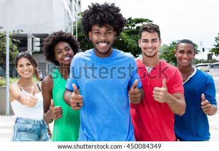 Group of international young adults showing thumbs in city - stock photo