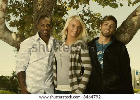group of 3 interracial friends standing by a tree - stock photo