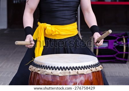 Group of japanese musicians are playing on traditional japanese percussion instrument Taiko or Wadaiko drums. The drumsticks are in the hands. - stock photo