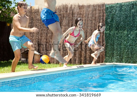 Group of joyful children jumping in a swimming pool in a home garden on a sunny summer holiday, having fun being energetic outdoors. Active kids lifestyle, playing in house exterior on vacation. - stock photo