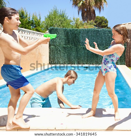 Group of joyful children playing by swimming pool in a home garden on a sunny summer holiday, having fun with water pistols outdoors. Active kids lifestyle, playing in house exterior on vacation. - stock photo