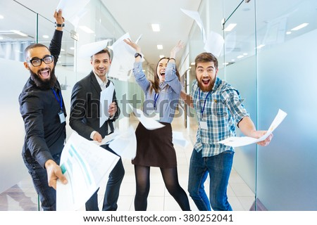 Group of joyful excited business people throwing papers and having fun in office - stock photo