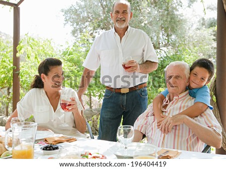 Group of joyful family members enjoying a Spanish tapas meal in a villa green garden while on a holiday in a summer home, eating and drinking together during a summer day, portrait outdoors. - stock photo