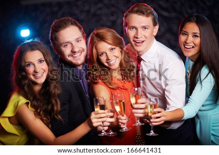 Group of joyful friends toasting with champagne in the bar