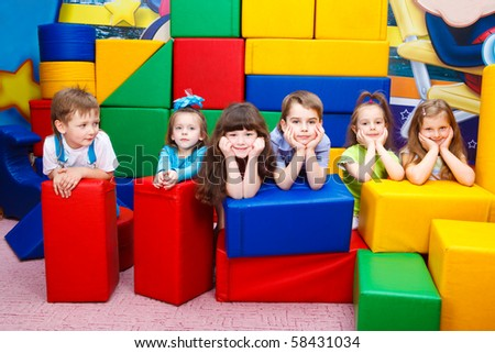 Group of joyful kids hiding behind large leather blocks - stock photo