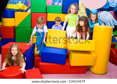 Group of joyful kids playing with large leather blocks - stock photo