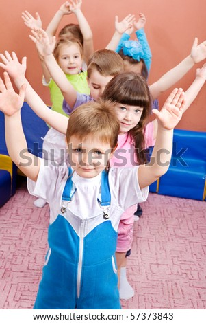 Group of joyful kids with their hands up