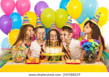 Group of joyful little kids celebrating birthday party and blowing candles on cake. Holidays concept. - stock photo
