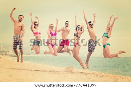 Group of joyful men and women jumping on a beach near blue sea on a sunny day