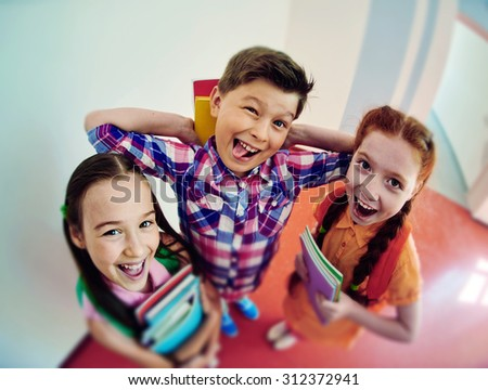 Group of joyful schoolkids with books looking at camera - stock photo