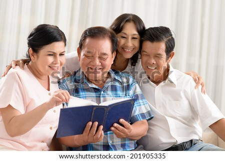 Group of joyful senior people watching a photo album - stock photo