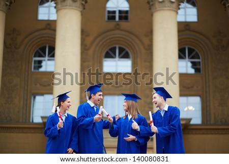 Group of joyful students in graduation gowns holding diplomas - stock photo
