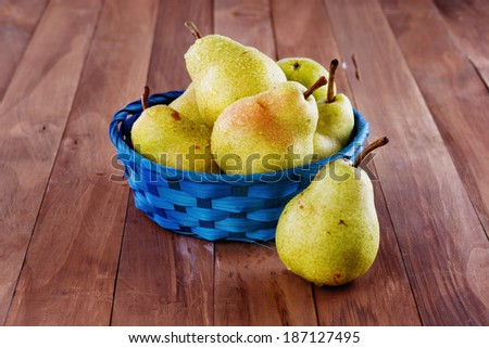 Group of juicy yellow pears in a blue woven basket on a wooden background - stock photo