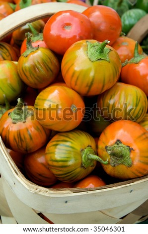 Group of just harvested heirloom tomatoes  in basket at local farm market - stock photo