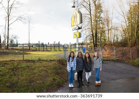 Group of kids at school crossing sign - stock photo