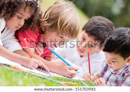 Group of kids coloring outdoors and looking happy  - stock photo