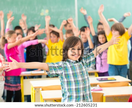 Group of kids having up rising hands with books in classroom - stock photo