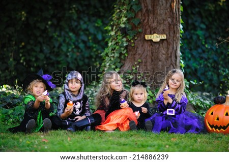 Group of kids in costumes on a Halloween party have a fun, trick or treat - stock photo