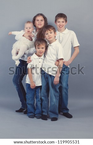 Group of kids in jeans on gray background, studio - stock photo