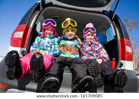 group of kids in winter clothes sitting in the trunk of a car - stock photo