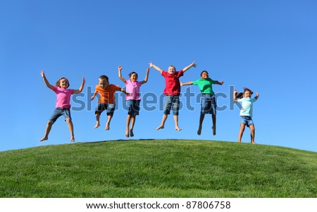 Group of  kids jumping on grass hill with blue sky - stock photo