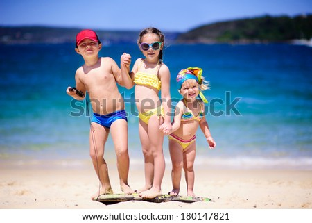 Group of kids on a sand beach at sun day - stock photo