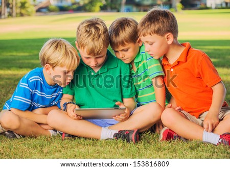 Group of kids on grass using tablet computer
