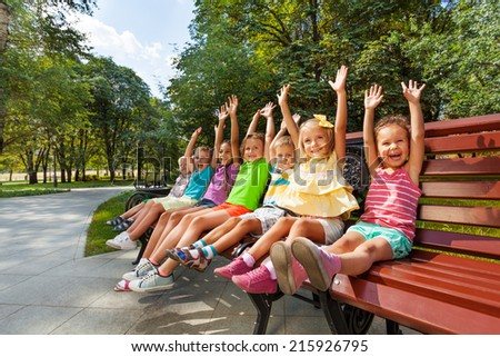 Group of kids on the bench cheering lifting hands - stock photo