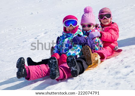 group of kids riding on snow slides in winter time - stock photo