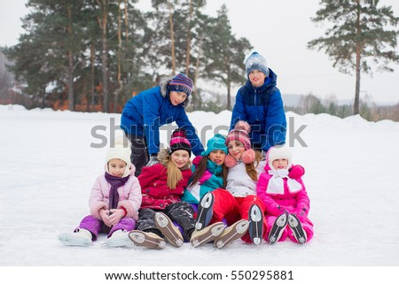 group of kids sitting on the ice of the frozen lake with forest on the background
