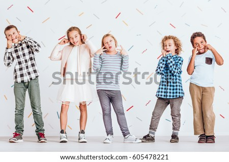 Group of kids standing next to each other and pulling faces