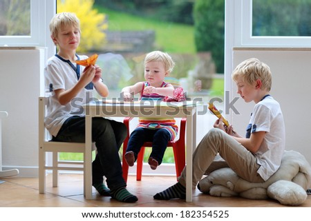 Group of kids, two twin brothers with little toddler sister playing indoors making paper planes sitting nearby big window with street view on a sunny summer day  - stock photo