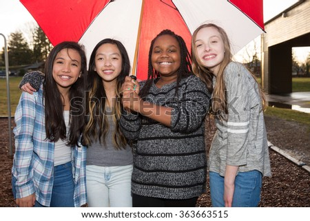 Group of kids under an umbrella in the rain - stock photo