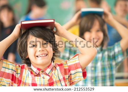 Group of kids with books on heads smiling in classroom - stock photo