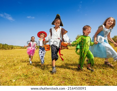 Group of kids with costumes running in park - stock photo