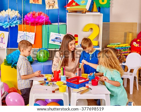 Group of kids with female teacher painting  together in  kindergarten .  - stock photo