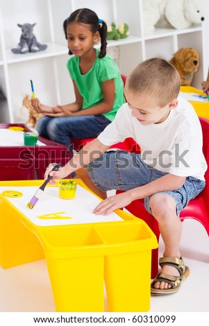 group of kindergarten kids painting - stock photo