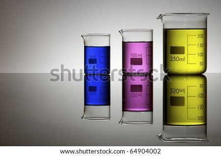 group of laboratory beakers containing liquid color