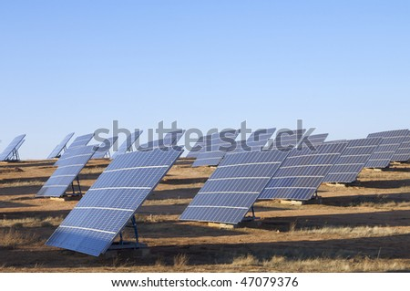 group of large photovoltaic panels with clear blue sky - stock photo