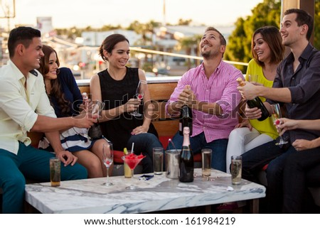 Group of Latin friends celebrating and popping a bottle of champagne at a terrace - stock photo